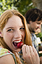 Germany, Bavaria, Upper Bavaria, Young woman in beergarden eating radish, portrait, close-up - WESTF09603