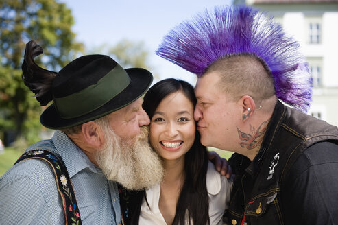 Germany, Bavaria, Upper Bavaria, Two men kissing Asian woman on cheek, portrait - WESTF09552