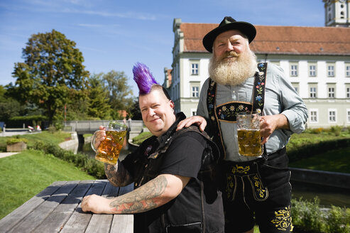 Germany, Bavaria, Upper Bavaria, Man with mohawk hairstyle and Bavarian man in beergarden - WESTF09546