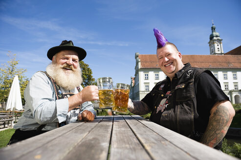 Germany, Bavaria, Upper Bavaria, Man with mohawk hairstyle and Bavarian man in beer garden - WESTF09543