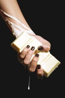 Female hand holding melting chocolate bar, close-up - OW00881
