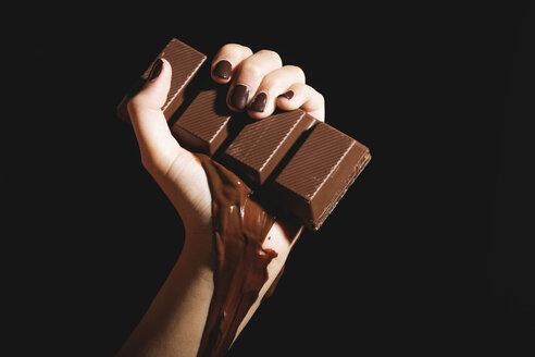 Female hand holding melting chocolate bar, close-up - OW00878
