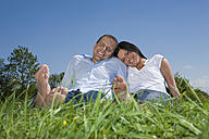Young couple relaxing in the meadow, smiling - CLF00590