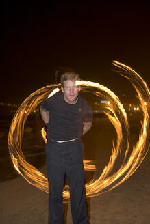 Spain, Canary Islands, Gran Canaria, Young man juggling with torches - PK00298