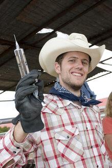USA, Texas, Dallas,, Cowboy holding syringe, smiling, portrait - PK00279