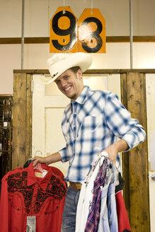 USA, Texas, Dallas, Young man choosing shirts - PK00245