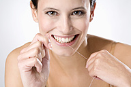 Young woman flossing her teeth, close up - MAEF01297