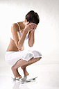 Young woman squatting on scales, hands to heas - MAEF01282