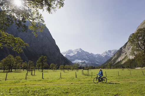 Austria, Karwendel, Senior woman biking - WESTF10525