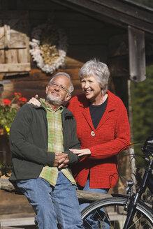 Austria, Karwendel, Senior couple in front of log cabin - WESTF10513