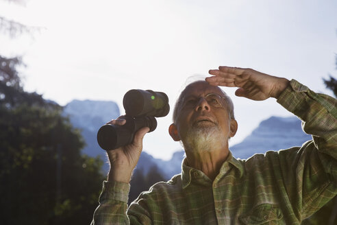 Austria, Karwendel, Senior man holding binocular, looking up - WESTF10501