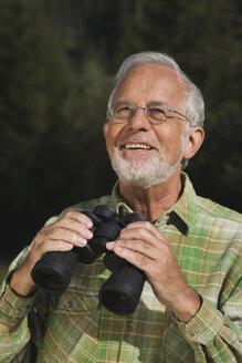 Austria, Karwendel, Senior man holding binocular, portrait - WESTF10498