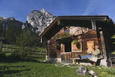 Austria, Karwendel, Senior man sitting in front of log cabin, reading a book - WESTF10495
