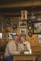 Senior couple sitting at table in Log Cabin - WESTF10420