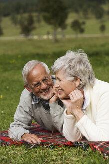 Austria, Karwendel, Senior couple relaxing in meadow - WESTF10408