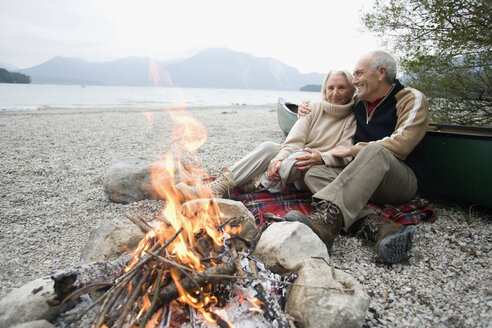 Germany, Bavaria, Senior couple sitting at campfire - WESTF10222