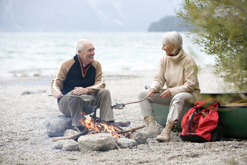 Germany, Bavaria, Senior couple sitting at campfire, grilling fish - WESTF10219