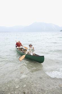 Germany, Bavaria, Walchensee, Senior couple rowing boat on lake - WESTF10216