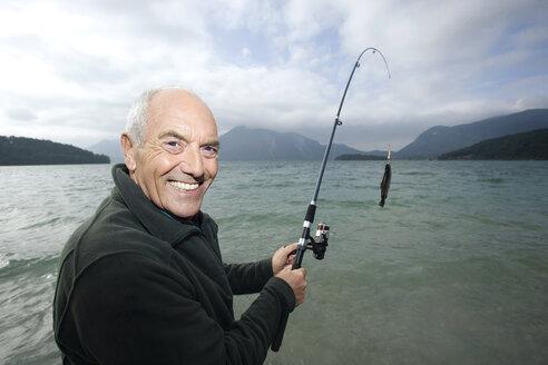 Germany, Bavaria, Walchensee, Senior man fishing in lake - WESTF10204