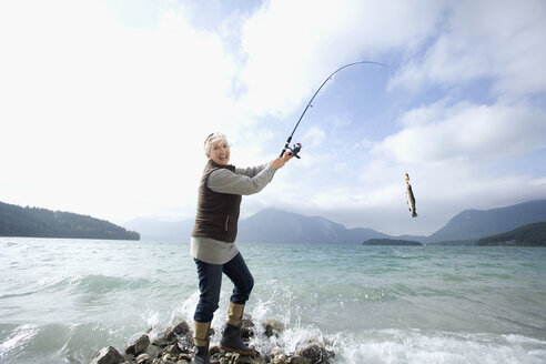 Germany, Bavaria, Walchsensee, Senior woman fishing in lake - WESTF10197