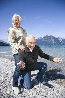 Germany, Bavaria, Walchenseel ,Senior couple fooling about on lakeshore - WESTF10152