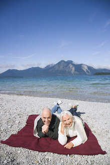 Germany, Bavaria, Walchensee, Senior couple relaxing on lakeshore - WESTF10146
