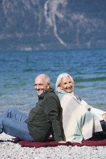 Germany, Bavaria, Senior couple relaxing on lakeshore, sitting back to back - WESTF10140