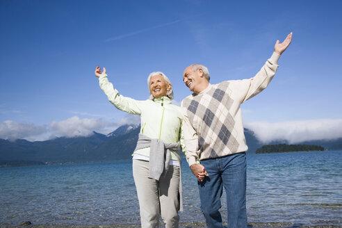 Germany, Bavaria, Walchensee, Senior couple cheering - WESTF10127