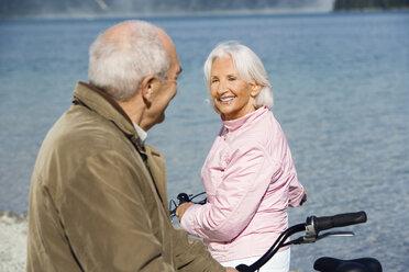 Germany, Bavaria, Walchensee, Senior couple pushing bikes across lakeshore - WESTF10106