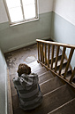 Boy (12 years) sitting in staircase, rear view - WDF00366