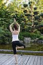 Germany, Bavaria, Munich, Young woman exercising yoga, rear view - NHF00969