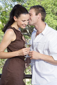 Young couple flirting, holding wine glasses, close-up - ABF00482