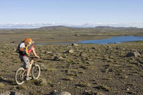 Iceland, Man mountain biking across lowland - FFF00960