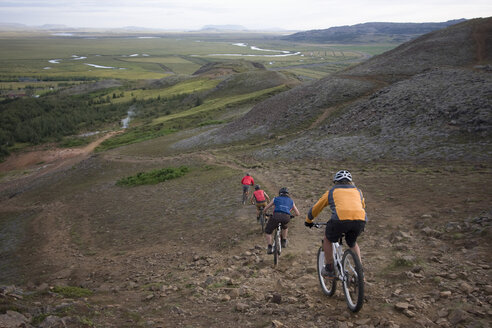 Iceland, Men mountain biking downhill, rear view - FFF00954