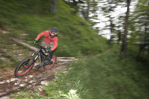 Germany, Bavaria, Chiemgau, Young man mountain biking at high speed - FFF00945