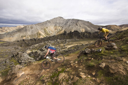 Iceland, Men mountain biking in hilly landscape - FF00995