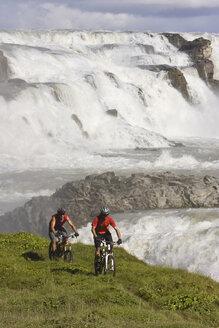 Iceland, Men mountain biking, waterfall in background - FF00986