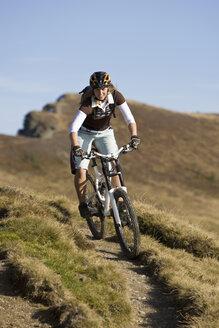 Austria, Salzburger Land, Zell am See, Woman mountain biking - FFF01026