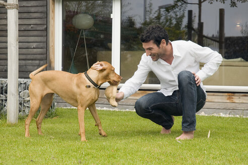 Young man playing with dog in garden - NHF01019