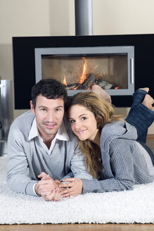 Young couple lying on carpet, in front of fireplace, smiling - NHF01007