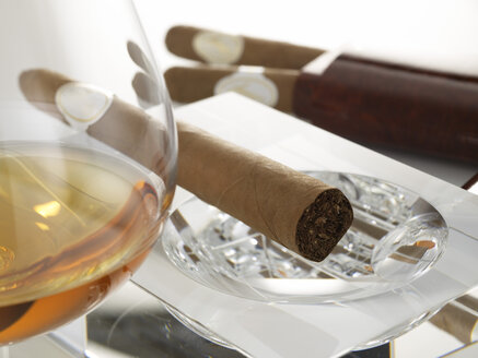 Cigar in ashtray with glass of cognac, close-up - AKF00075