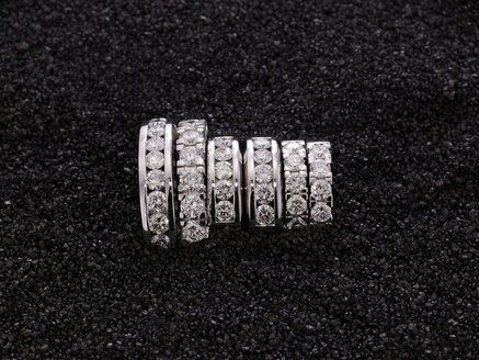 Diamond rings on black sand, elevated view - AKF00021
