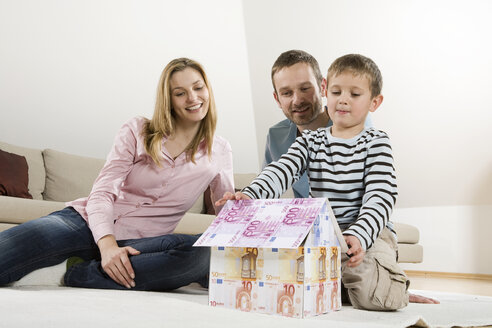 Parents and son (4-5), building house from Euro notes - CLF00678