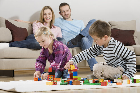 Family at home, children playing with building bricks - CLF00675