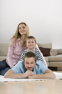 Parents and son (4-5) at home, smiling, portrait - CLF00669
