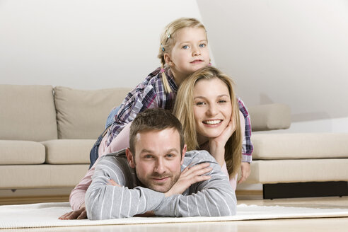Parents and daughter (3-4) relaxing at home - CLF00654