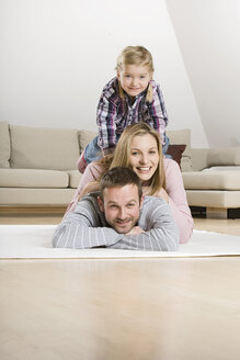 Parents and daughter (3-4) relaxing on carpet, portrait - CLF00651