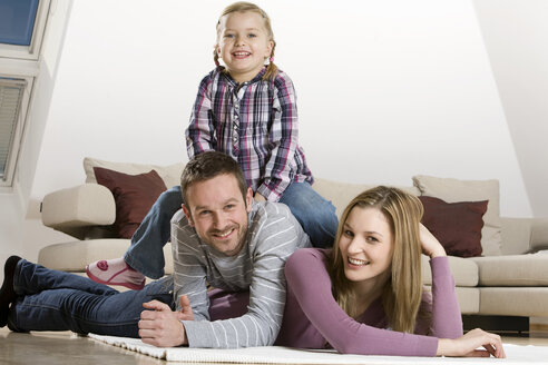 Parents and daughter (3-4), relaxing at home - CLF00645