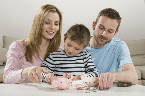 Parents and son (4-5) looking at broken piggybank, counting money - CLF00627