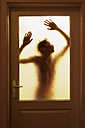 Silhouette of young man behind glass door - WW00429